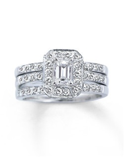 Round diamonds frame a stunning emerald-cut diamond, the focal point of this beautiful engagement ring. Additional round diamonds decorate either side of the 14K white gold band. The two matching wedding rings, to be worn on either side, are showered in diamonds. This wedding set has a total diamond weight of 1 1/5 carats.