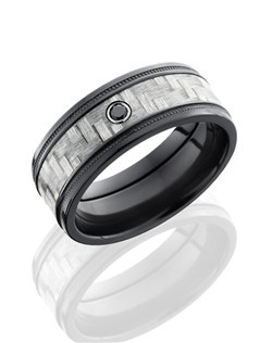 This remarkable Black Zirconium men's wedding band is 9mm wide with a custom flat design with grooved edges. This ring contains two wide set milgrain grooves and one 5mm Silver Carbon Fiber inlay with one bezel set .05 black Diamond. Bring out the best in him with this impressively intricate ring.