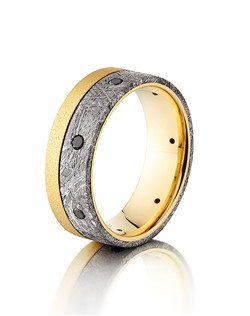 This remarkable 18K Yellow Gold men's wedding band is 8mm wide with a custom flat design. This ring contains an off centered meteorite inlay with seven, flush set .04 black Diamonds.  This modern design is sure to capture attention and is durable enough to last a lifetime.