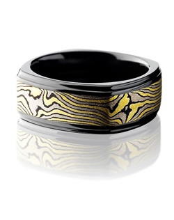 This remarkable Black Zirconium men's wedding band is 8.5mm wide with a custom flat square design and grooved edges. This ring contains 18K Yellow Gold, 14K White Gold and Sterling Silver all bonded together and twisted to create this Mokume Gane pattern. Let this impressive ring bring out the best in him.