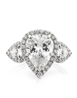 This exquisite one of a kind pear shaped diamond ring will mesmerize you with its design, quality, craftsmanship and the size of this incredible diamond! The 3.52ct pear shaped diamond set in the center is GIA certified (one of the leaders in diamond grading) at H-SI2, white and eye clean! The cut is phenomenal! It has such an amazing shape and the facets are impeccable! The brilliance and fire will astonish you. The custom-made platinum setting features a halo of round diamonds set around the center. It is flanked by two large pear shaped diamonds with a halo around each of them which leads to round diamonds set down the shank in a micropave setting. The center basket is studded with round diamonds as well. This mesmerizing work of art will captivate you upon first sight! It is just jaw dropping!