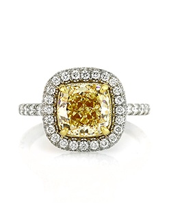 This remarkable fancy yellow cushion cut diamond engagement ring will astonish you with its design, quality and craftsmanship! The mesmerizing 2.52ct cushion cut diamond set in the center of this magnificent custom crafted platinum setting is GIA Certified, one of the leaders in diamond grading, at Fancy Yellow VS1. It has such a vibrant and beautiful fancy yellow color and amazing clarity. The cut is exceptionally beautiful and it sparkles tremendously! It is accented by a row of round diamonds set around it and a row set on the sides of the halo in a gorgeous micropave setting with minimal metal showing. The shank is set with a row of round diamonds as well. The mesmerizing center basket is hand crafted to perfection in 18k yellow gold and is hand engraved throughout. The connectors are also studded with round diamonds for an added touch of brilliance. Simply sensational! You will cherish it forever.