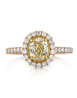 Yellow diamond and rose gold make for a wildly beautiful color combination in this gorgeous engagement ring. The center of this ring features a 1.00ct oval cut EGL diamond certified at Fancy Light Yellow, VVS2. The lemon yellow color of the one carat center stone is quite desirable and the cut is simply brilliant. This colored diamond is set in a hand engraved yellow gold basket surrounded by a halo of micropave set round diamonds. The shank of this 14k rose gold ring is also embellished with a row of diamonds in a micropave setting. This is a truly exquisite, original engagement ring she will treasure for a lifetime!
