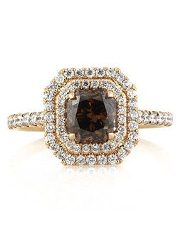 Beautiful rose gold and fancy brown diamonds make for an intensely rich color combination on this phenomenal double halo diamond engagement ring. Featured in the center is a 1.41ct radiant cut diamond that is GIA certified at Fancy Dark Orange Brown- SI1. The color is a dark, lovely brown and the cut a gorgeous old mine-like cut with a taller crown. The almost one and a half carat center diamond is encompassed by a double halo of round brilliant cut diamonds set in a micropave setting. There are more round diamonds set down the dainty shank and on the connectors of this 18k rose gold setting giving it incredible sparkle. This exquisite engagement ring will be the envy of all whom lay eyes on it!