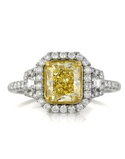 This mesmerizing fancy yellow radiant cut diamond engagement ring will take your breath away! The magnificent 1.54ct radiant cut center diamond is GIA certified at Fancy Yellow VVS2. The pure yellow is so vibrant and beautiful, and it is practically flawless! This diamond has an incredible sparkling cut. It is accented by a halo of round diamonds in a micropave setting and two step cut trapezoids flanked on its sides with a row of round diamonds set around them as well. There is a row of round diamonds set down the shank. The center basket is studded with a round bezel set diamonds on each side and elegant handmade filigree accents. It is absolutely beautiful! You are going to cherish it forever.