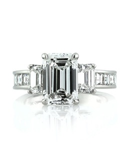 This magnificent emerald cut diamond engagement ring will knock you off your feet with its amazing beauty and extravagant quality! The exquisite 2.50ct emerald cut diamond poised in the center is GIA certified at E-VVS1, colorless and near flawless! The cut of this two and half carat emerald is absolutely brilliant and stunning. The two emerald cut side diamonds totaling 1.02ct are also GIA certified E-VVS1, a perfect match to the high quality center stone. The emerald diamonds are arranged in a three-stone fashion atop this custom platinum setting. Colorless step cut or carré cut diamonds are channel set down the shank providing extra sparkle to this one of a kind ring. This astonishing emerald cut diamond ring is of true heirloom quality and will be garnering compliments for generations!