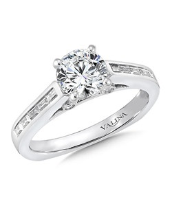 Channel-set baguette diamond shoulders flank the center stone. The cathedral solitaire design is accented with bezel-set diamonds set in the under gallery for a unique look. This engagement ring is part the Eternal Collection. Mounting with side stones .27 ct. tw., 1 ct. round center. Price excludes center stone.