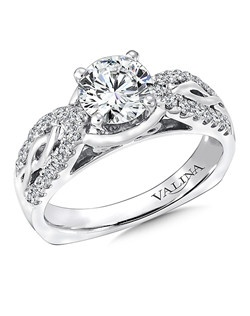 Wide pinched diamond shoulders frame an open polished infinity symbol that draws your eye to the stunning center stone. The filigree gallery adds the a special touch. This ring is part of the Graceful Collection. Mounting with side stones .28 ct. tw., 1 ct. round center. Price excludes center stone