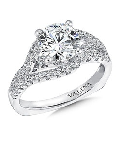 A split bridge of diamonds bypasses and frames the center stone while a single row of stones below maximizes the ring's sparkle. Mounting with side stones .67 ct. tw., 1 1/2 ct. round center.Price excludes center stone