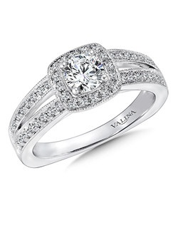 Two diamond bands flare and meet a sparkling cushion shape halo that surrounds the center stone. A surprise diamond and milgraine trim adds an heirloom feel. Cushion shape halo mounting .26 ct. tw., 1/2 ct. round center.  Price excludes center stone