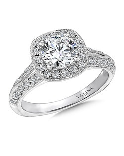 This all pave-set diamond ring , lights up the center stone. It's cushion shape halo and beveled milgraine finish split shoulders with infinity motif in the gallery add a vintage touch.   Cushion shape halo mounting .43 ct. tw., 1 ct. round center.  Price excludes center stone