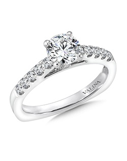 The raised fish tail-set shank sets the perfect stage for the dazzling center diamond in this classic solitaire ring design. Mounting with side stones .26 ct. tw., 3/4 ct. round center.Price excludes center stone