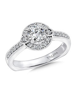 A diamond halo with pear shape motifs lights up the center stone. Pave-set diamond shoulders and milgraine finish complete the vintage look. Round halo mounting  .25 ct. tw.,  1/2 ct. round center.Price excludes center stone