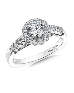 The raised diamond shoulders sets the stage for the round center. A diamond encrusted gallery and scalloped airlines make for a unique design. Round halo mounting  .47 ct. tw.,  1/2 ct. round center.Price excludes center stone