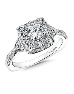 Deco inspired details and diamond accents frame the center stone.  A sparkling triangle motif and pinched diamond shoulders flank the sides of this beautiful vintage inspired ring. Floral shape halo .32 ct. tw., 1/2 ct. round center.Price excludes center stone