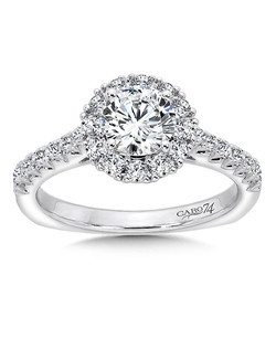 14K White Gold CARO 74 RING with platinum head. A luminous diamond center stone is  wrapped in a round diamond halo. Diamond side stones flow down the ring's shoulders in this elegant design.   Also available in white gold, yellow gold, 18K and Platinum. Price excludes center stone