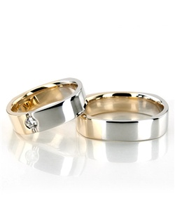 A Four-sided Two-tone his & hers set. His ring is 5mm wide. Her ring is 5mm wide and set with 1 Round Brilliant Cut Diamond. Diamond weighs 0.1ct. The diamond is graded G in color and SI1 in clarity. The band is partially high polished, and partially satin finished.