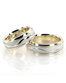 This beautiful 6.5mm wide Two-tone wedding ring set is a favorite thanks to its elegant design. It has a wave-shaped bright cut going all around the center piece. Center of the band is brush finished. Each side is high polished.