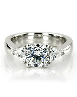 Charming! This gorgeous three stone diamond engagement ring is prong set with 2 trillion cut diamonds totaling 0.70 ct.tw. The diamond ring features a 1.00 ct.tw round cut diamond in the center. This diamond engagement ring is available in white gold, yellow gold, platinum or palladium.