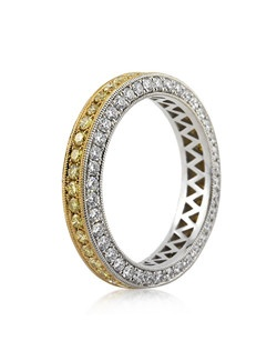 This gorgeous custom-made fancy yellow and white diamond eternity band will mesmerize you with its brilliance, beauty and craftsmanship. A row of fancy yellow diamonds are set on top of the band in a pave setting. The front and back is set with white diamonds in a pave setting. The ring is made in high polish platinum and features handmade milgraining throughout. A perfect wedding band to accent your engagement ring and a great stand alone band as well!