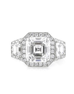 This mesmerizing Asscher cut diamond engagement ring is astonishing! The gorgeous 3.08ct Asscher cut center diamond is elegantly accented by two large trapezoid side diamonds. There are round diamonds set around the center stone and side stones in a beautiful pave setting. The sides of the engagement ring feature a row of round diamonds along with the center basket. This gorgeous piece features clean lines, exceptional quality and detail and tremendous brilliance. A piece you will cherish forever!