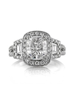 This astonishing cushion cut diamond engagement ring will mesmerize you with its fine details and magnificent quality! The 2.06ct cushion cut center diamond is GIA certified at D-VS2. It is exceptionally white, perfectly clear and has an excellent cut! This amazing diamond is showcased beautifully in this high polish 18k white gold setting featuring a halo of round diamonds in a pave setting flanked by two gorgeous step cut trapezoids and accented by round brilliant cut diamonds. The double shank is set with round diamonds as well. The unique center basket is elegantly designed with handmade filigree accents with a round diamond pave set in the center and milgrain detail throughout. This spectacular piece is sure to be cherished forever!