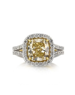 This gorgeous fancy yellow cushion cut diamond ring is breathtaking from every angle! The magnificent 3.28ct cushion cut diamond is GIA Certified at Fancy Light Yellow SI1. It has a rich and vibrant canary yellow color and it is spectacularly brilliant! A halo of round brilliant cut diamonds accents it and there are two rows of round diamonds set down the shank. The bottom of the shank and center basket are both hand engraved to perfection with tremendous detail and beauty. It is exquisite! An astonishing piece that you won't be able to take your eyes off of! Get ready for the compliments.