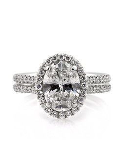 This astonishing oval cut diamond ring is extraordinary in so many ways. It features a mesmerizing 2.01ct oval cut diamond poised in the center. It is GIA certified, one of the leaders in diamond grading, at E-VS1. It is very white and perfectly clear, even under 10X magnification. The cut is outstanding as well. It sparkles tremendously! The beautiful custom-made setting showcases it perfectly. It features a halo of round diamonds set around the center and two rows of round diamonds set down the shank in a micropave setting. The center basket features handmade filigree designs with round diamonds studded on the connectors. It is so exceptionally beautiful! This very unique oval cut diamond ring is sure to make jaws drop wherever you go!