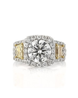This outstanding round cut diamond ring is masterfully designed with a unique fancy yellow twist! The stunning 2.04ct round brilliant cut center diamond is EGL certified at F-SI2. It is exceptionally white and incredibly brilliant! It is certified as an Ideal Cut diamond, which means the proportions are perfect, and it gives off optimal brilliance! It is accented by two large brilliant cut trapezoids that are fancy yellow in color with round diamonds surrounding each of them. The split shank is set with two rows of round diamonds in a micropave setting and we added additional round diamonds on the center basket area as well for an added touch of sparkle. It is mesmerizing in so many ways! You will love this exceptionally unique piece!
