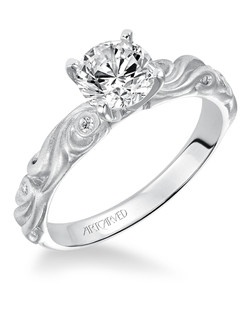 Hayley, Vintage Inspired Diamond Engagement Ring with Round Center and a Satin Finished Floral Carving Detail Highlighted with Diamonds.  Available in Platinum, 18K and 14K gold. Price listed below is for the setting only. Total weight of semi-mount .04 Ct. Settings can be custom made to fit any size or shape center stone. Matching band available - Style numbers V100W-L and V100W-W