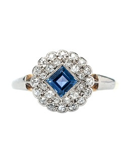 Lockwood is sweet little Victorian era platinum topped 18k yellow gold ring centering a bezel set, Square Step Cut natural sapphire weighing approximately 0.40ct. set on an angle. This pretty center stone is accented by a double circular halo of twenty-eight Single Cut diamonds totaling approximately 0.20ct. The gallery is decorated with subtle, scalloped filigree and a simple platinum and gold slightly tapered shank. Lockwood is currently a size 8 and can be sized to fit.
