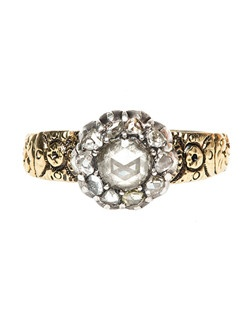 Larchmont is a beautifully unique platinum and 18k yellow gold antique ring from the turn of the 19th century. The ring centers a bead set Rose Cut diamond gauged at approximately 0.65ct, graded K-L color and VS clarity. This beautiful center diamond is further decorated with a delicate halo of ten Rose Cut diamonds totaling 0.25ct. As a finishing touch, the 18k yellow gold shank is elegantly designed with stunning abstract hand engraving. Larchmont is currently a size 10 and can be sized to fit.