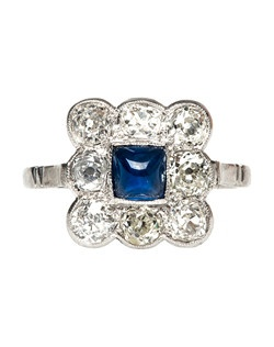 Sugar Beach is a glamorous Edwardian platinum-set ring centering a bezel set natural Sugarloaf Cabochon Sapphire gauged at approximately 0.70ct. This gorgeous sapphire is surrounded by a square halo of eight bezel and prong set Old Mine Cut diamonds with a total estimated weight of 1.60ct, graded I-L color and VS/SI clarity. Sugar Beach is further accented by delicate milgrained edges, a simple shank and a touch of floral filigree throughout the gallery. This ring is currently a size 7.75 and can be sized to fit!