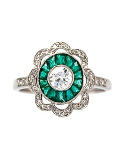 Mount Vernon is a beautiful Art Deco platinum set engagement ring centering a bezel set Old European Cut diamond gauged at 0.33ct graded H-I color and SI clarity. Surrounded by a bright green halo of fourteen Calibre Cut emeralds totaling about 0.40ct., Mount Vernon is further decorated with a scalloped halo of thirty-four Single Cut diamonds totaling approximately 0.15ct. We absolutely love the color contrast of the sparking white diamonds mixed with the incredibly saturated natural emeralds! Mount Vernon is currently a size 6 and can be sized to fit.
