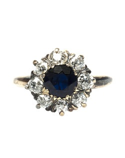 Pawley's Island is a romantic Victorian era cluster ring featuring an exquisite 0.75ct round natural dark blue sapphire mounted in a 14k oxidized yellow gold setting, further surrounded by a decadent halo of eight sparkling Old Mine Cut diamonds totaling approximately 0.75ct. Pawley's Island is currently a size 4 and can be sized to fit.