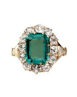 Clover Creek is a gorgeous Victorian era 18k yellow gold cocktail ring centering a pale Step Cut emerald gauged at 2.50ct., accompanied with a Guild Laboratories certificate stating that the emerald is of Colombian origin. Clover Creek is surrounded by a decadent halo of twelve Old Mine Cut diamonds totaling approximately 1.20ct, graded G-H color and SI clarity and is further enhanced with an 18k yellow gold split shank. Clover Creek is currently a size 6.5 and can be sized to fit.