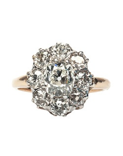 Sterling Ridge is a showstopping Victorian era cluster ring made from platinum topped 18k yellow gold. This elegant ring scintillates from every angle, centering an exquisite 1.19ct EGL certified Old Mine Cushion Cut diamond graded H color and VS1 clarity, surrounded by a delicate halo of eight additional Old Mine Cut diamonds totaling approximately 1.60ct in weight graded G-I color and SI clarity. This timeless halo ring will make a sparkling statement on any woman's hand and is another house favorite at T&H! Sterling Ridge is currently a size 5.5 and can be sized to fit.