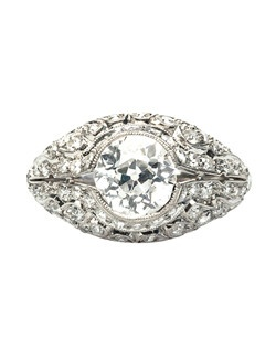Buckingham is a stellar example of Edwardian era design! This stunning engagement ring is made from platinum and centers a bezel set 1.59ct EGL certified Old European Cut diamond graded E color and VS2 clarity. The exceptional quality and size of the center diamond was very rare and unique for this period. Buckingham's bombe style setting is further adorned with sixty four Single Cut diamonds totaling approximately 0.75ct, graded E-F color and VS clarity, and is completed with beautiful milgrained edges and a tapered shank. Buckingham is currently a size 6.5 and can be sized to fit most ring sizes.