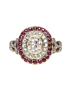 Montmartre is a show stopping Edwardian era engagement ring made from 18k yellow gold and platinum featuring rubies and diamonds in a double halo setting. This beautiful ring centers a bezel set Old Mine Cut diamond weighing approximately 0.70ct graded K-L color and SI clarity, surrounded by a halo of sixteen Rose Cut diamonds totaling approximately 0.18ct, and a second halo of thirty four round natural rubies with an estimated weight of 0.30ct. The shoulders of Montmartre are decorated with a platinum and diamond studded floral motif, complete with French Hallmarks on the outside of the shank. Montmartre is currently a size 4.25 and can be sized to fit.