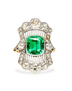 Montgomery is an intricately designed antique Edwardian engagement ring made from platinum and 18k yellow gold.  This cocktail style navette ring features a spectacular bezel set cushion shaped natural Colombian emerald. The show stopping center stone is certified by Guild Laboratories and measures 9.3mm x 8.3mm x 3.9mm. Two artfully curved rows of bead set Single Cut diamonds and platinum filigree work suspend six sparkling Old European Cut diamonds to complete a dramatic scalloped frame on this exquisitely unique and unusual engagement ring. Two additional Old European Cut diamonds anchor the position of the stunning 18k gold band for a total of 3.00cts in total diamond weight. Montgomery is currently a size 7 and can be sized to fit.