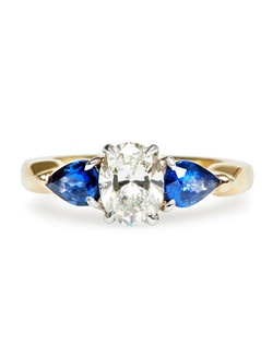 Innsbrook is a stunning vintage 1980's decade ring made from 18k yellow gold centering an EGL certified Oval Cut diamond weighing exactly 1.00ct, graded G color and VS2 clarity. Flanked on either side of this memorable sapphire engagement ring are two pear shaped natural bright sapphires with a total approximate weight of 0.85ct. This three stone wedding ring is complete with chunky contoured shoulders made from 18k yellow gold and platinum prongs. Innsbrook is currently a size 6.25 and can be sized to fit.