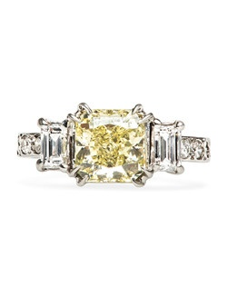 Sunny Springs is an incredible vintage colored gemstone engagement ring set in platinum featuring a stunning 1.73cts GIA certified Radiant Cut Fancy Yellow diamond graded VS2 clarity. This classic design features the show stopping center stone in a talon-prong setting that is flanked on either side by two Emerald Cut diamonds weighing approximately .50ct. An additional six Round Brilliant Cut diamonds decorate the shank, giving Sunny Springs a truly glittering presence. Sunny Springs is currently a size 5 and can be sized to fit.