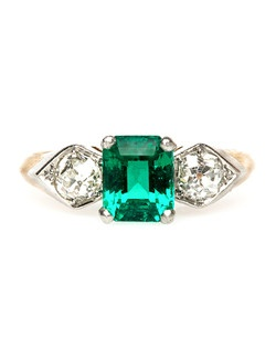 Garden Park is a gorgeous Edwardian era emerald ring made from platinum topped 14k yellow gold. Garden Park features a 1.46ct GIA certified Step Cut Columbian emerald, nestled between two Old Mine Cut diamonds set in a shield shape setting totaling approximately 0.55ct. This beautiful ring is a Brock & Co. original and is stamped inside the shank. Garden Park is currently a size 6.5 and can be sized to fit.
