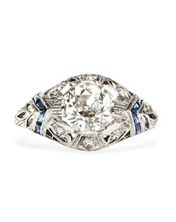 Fox Lake is a spectacular vintage Edwardian Era engagement ring made from platinum, featuring a 1.45cts EGL certified Old European Cut main diamond, graded J color and SI1 clarity. This incredible sapphire engagement ring is ornately decorated with milgrained edges, foliate filigree, and linear engraving throughout the shank and shoulders. Fox Lake is further enhanced with six Single Cut diamonds with an approximate weight of 0.18ct and four Calibre Cut sapphires in a chevron pattern, weighing approximately 0.20ct. Size 6.5. This ring can be sized to fit!