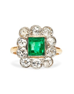 Montrose is a playful antique Victorian era engagement ring made from 18k yellow gold and topped in platinum. Montrose features a charming Rectangular Step Cut emerald with an approximate weight of 1.20cts. This vibrant halo engagement ring features the bright green center stone framed by ten Old European Cut diamonds weighing approximately 1.40cts. During the mid-Victorian Era, beautiful emeralds as featured in Montrose were the gemstone of choice. Montrose is currently a size 5.25 and can be sized to fit.