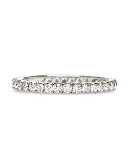 "This stunning, handmade wedding band is a vintage inspired Trumpet & Horn original and we are ecstatic to have this incredibly unique style in our collection. Although this ring may appear to be a standard diamond eternity band on first glance, each individual Round Brilliant Cut diamond is prong set with a beautiful fan-like pattern of platinum on each side; a historically significant technique called ""French Set"". The French Set technique was first used in the late 1500's, adding an undeniably distinctive antique touch to this otherwise simple and classic diamond wedding band. Size 6 features thirty-five Round Brilliant Cut diamonds weighing exactly 0.66ct graded F-G color and VS1 clarity. Each band is 1.7mm in diameter, but the total diamond weight will change depending on the size of the band that is ordered. This ring is made to order."