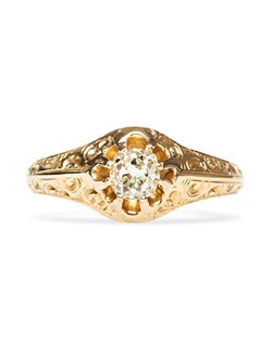 Elkhorn is a simple antique Victorian era engagement ring made from 18k yellow gold centering a 0.57cts Old Mine Cut diamond with an approximate color of M-N and SI clarity. The romantic diamond in this unique and inexpensive engagement ring gives off a subtle warmth.  This solitaire engagement ring showcases the center stone cradled in a dramatically raised eight prong cathedral setting with highly polished shoulders and an intricate hand-pierced gallery of scrolling filigree. Elkhorn is currently a size 7.75 and can be sized to fit.