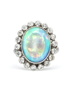 Baldwin is a one-of-a-kind vintage inspired ring made from 18k white gold centering a substantial oval cabochon opal gauged at 14.9mm x 11.6mm. This semi-transparent opal eluminates a wonderful display of red, blue, green and orange play of color. A delicate halo of nineteen Round Brilliant Cut diamonds further decorate the ring, each bezel set with milgrained edges. An additional six round diamonds cascade down the shoulders of the shank totaling approximately 1.00ct, graded G-H color and SI clarity. Baldwin is currently a size 6.25 and can be sized to fit.