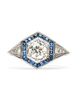 Bayfield is an extraordinary vintage geometric Art Deco era engagement ring made from 18k white gold, featuring a beautiful 0.66ct EGL certified Old European Cut diamond, graded I color and VS2 clarity. This gorgeous sapphire engagement ring highlights the center stone with a hexagonal border of twenty-four stunning Square Cut sapphires with a total approximate weight of 0.60ct.  The entire frame of sapphires on this unique halo engagement ring are enhanced with delicate milgrained edges. An additional six Old Full Cut diamonds with a total weight of 0.20ct accent the shoulders of this incredible ring. Bayfield is currently a size 5.5 and can be sized to fit.