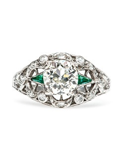 Weatherford is a dramatic vintage Art Deco era engagement ring set in platinum featuring a 1.27cts EGL certified Old European Cut diamond graded J color and VS1 clarity. The center stone of this unique and unusual engagement ring is nestled between two triangular emeralds. Twelve substantial Singular Cut diamonds are set within crescent shape motifs. This intricate emerald engagement ring is accented with delicate filigree work and hand-engraved foliate design throughout the shank and shoulders. Weatherford is currently a size 5.75 and an be sized to fit.